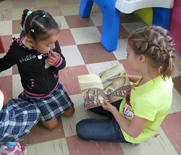 Young missionary Camy Boyll reading to a girl in Belize