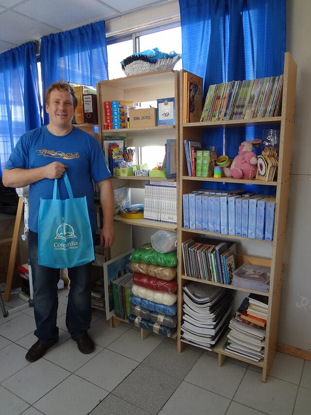 Rev. Omar Kinas happily posing with the church's new library