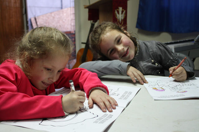 Two girls enjoy putting the church's new coloring books to use.