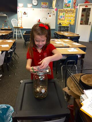 A Salem student changing the world by adding her change to her class's jar.