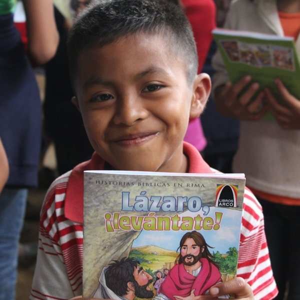 A young boy very happy to have his own copy of Lazaro, ¡levántate!