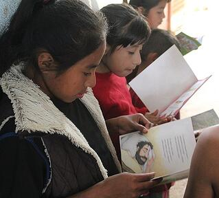 Guatemalan girls enjoy reading their new Arch Books.